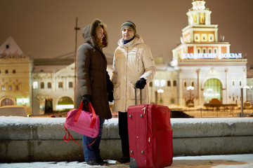 Young couple with big red trolley bag stands in evening