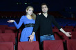 Young man and woman watch movie and are confused in cinema