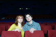 Young man and woman watch movie and surprise in cinema