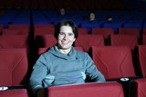 man sits in big cinema theater and looks at camera