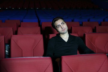 Young serious man in watches movie in big cinema theater.
