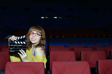 Happy beautiful woman in red glasses holds clap board