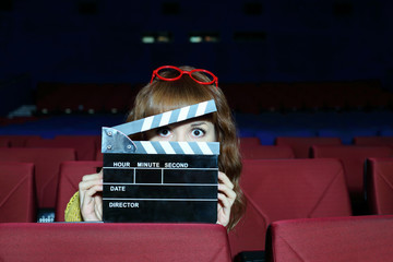 Happy beautiful woman looks through clap board in auditorium