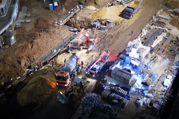 Cement mixer, crane and bulldozer at construction site at night.