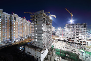 Lit high multi-storey buildings under construction and cranes