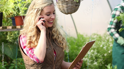 Pretty blonde buying plants following a list