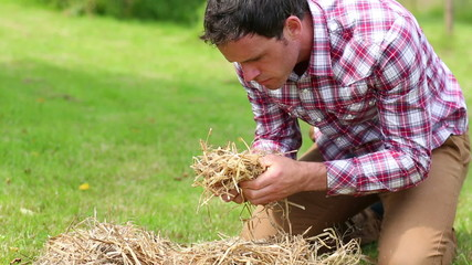 Smiling man touching and smelling straw