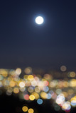 Full Moon Rise Over Blurred City Lights