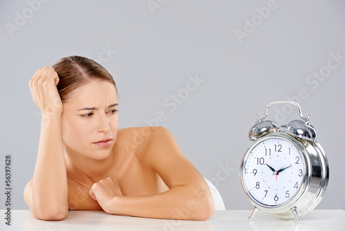 Woman looking at an alarm clock in consternation
