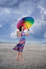 Barefooted woman with colorful umbrella under the rain