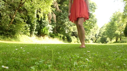 Beautiful teen walking on the grass on a sunny day