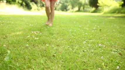 Female legs on the grass walking towards camera
