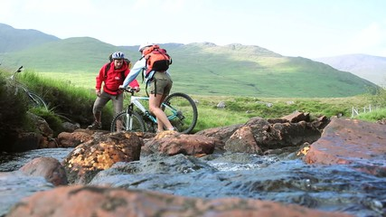 Couple crossing a stream together with their bikes