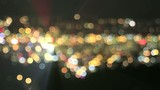 Defocused City Lights with Moving Car Beams Colorful Bokeh