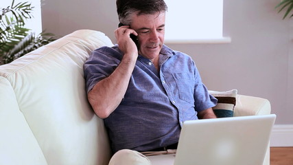 Mature man using laptop and answering the phone