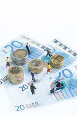 Miniature people on top of Euro banknotes and coins top view