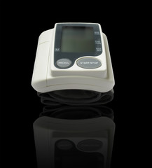 Digital blood pressure monitor on black background