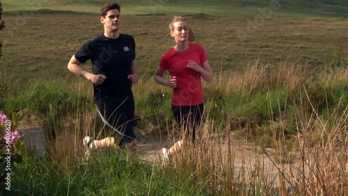 Athletic couple jogging on a country trail