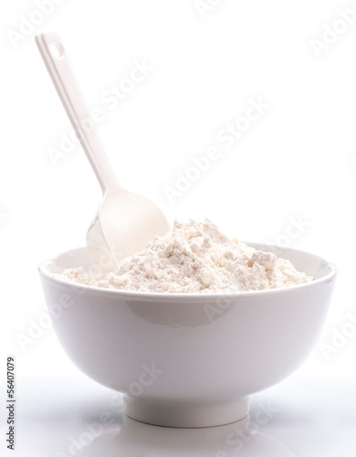 porcelain white bowl with spoon full of flour