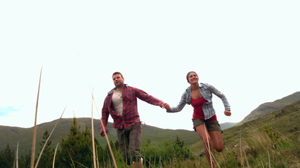 Happy couple running hand in hand though the countryside