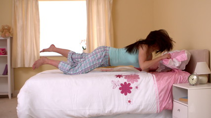 Attractive young woman jumping on her bed