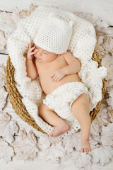 Newborn baby sleeping in white woolen hat
