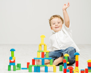 Child playing toys blocks over white