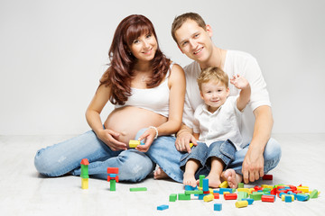 Happy family. Parents with kid playing toys blocks