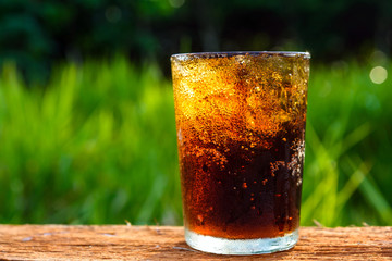cola with ice in glass against blur nature background