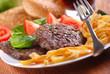 hamburger con contorno di patate fritte e pomodoro