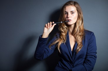 Elegant woman smoking e-cigarette wearing suit