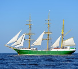 old historical green tall ship with white sails in blue sea