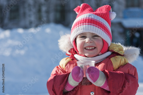 A small child is drinking a hot drink in winter