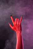 Heavy metal gesture, red devil hand with black nails