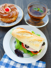 Breakfast with sandwich, tea and cake