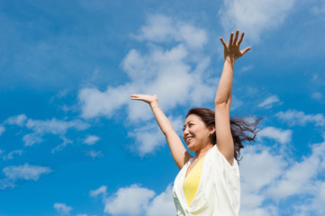 青空に向かって手を広げる白い服の女性
