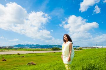 青空と雲と芝生と女性