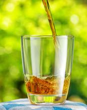 Un verre de jus de pomme sur fond de nature
