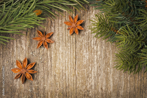 Christmas frame (spruce branches and star anise) on the old wood
