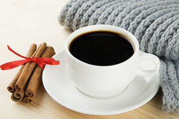 Cosy winter. Cup of coffee with scarf and cinnamon