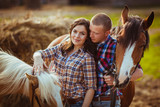 couple standing on farm with horses - 56434018