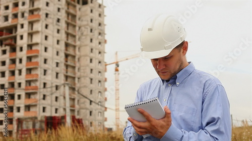 construction engineer writes in a notebook