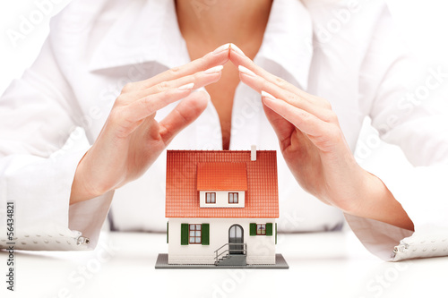 Female hands saving small house with a roof
