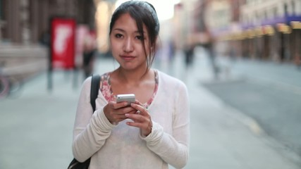 Asian woman texting on a street walking