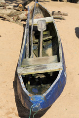 Single dugout blue canoe on the beach