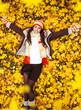 Woman lying on yellow leaves
