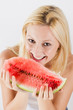 Beautiful blonde woman eating fresh watermelon