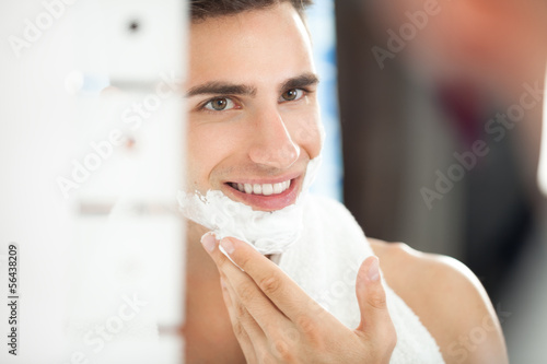 young man applying shaving cream to his face