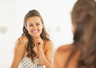 Smiling woman looking in mirror in bathroom