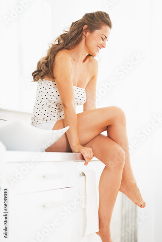 Portrait of happy young woman sitting in bathroom